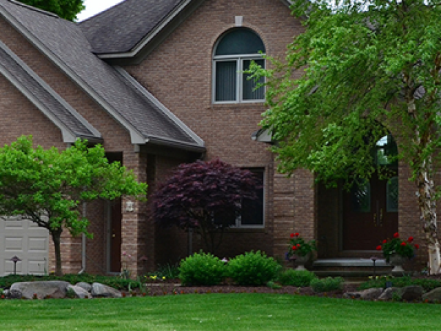 Front yard of St. Clair home with trees